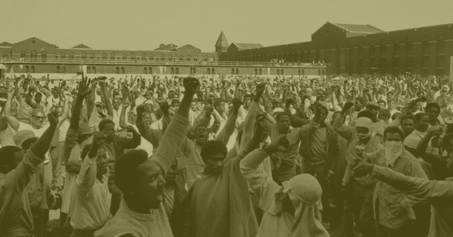 Photograph of Attica Prison Rebellion: Crowd of men with fists raised in air.