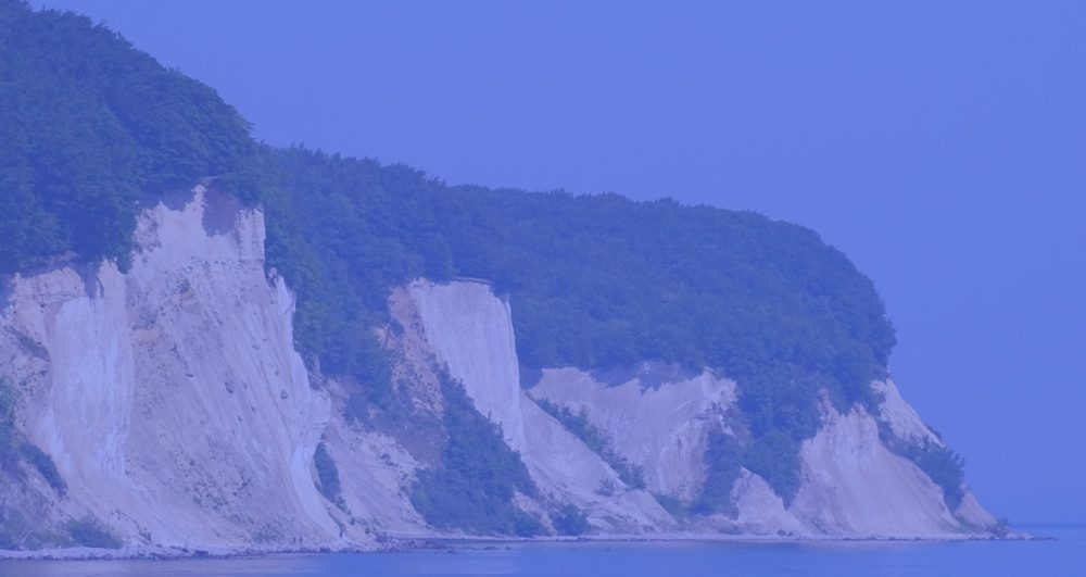 steep cliff overlooking water, blue overlay