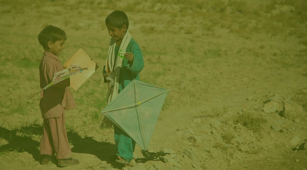 Two young Afghani boys standing in desert, each holding a kite.